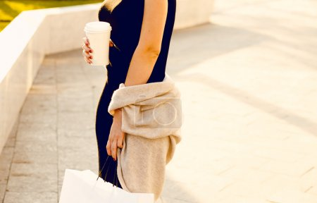 Photo pour Portrait de mode de jeune femme hipster avec chapeau et lunettes de soleil sur la plage au coucher du soleil, tons de couleur de style rétro saison froide. Des vêtements chauds. Tasse à café à emporter, couleurs du coucher de soleil, robe noire - image libre de droit