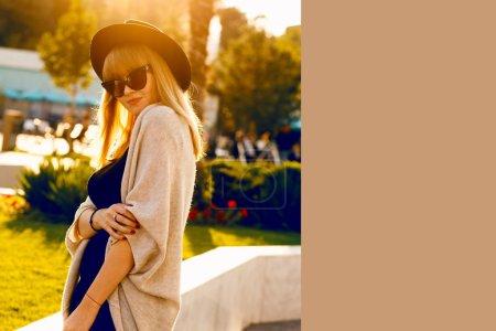 Photo pour Look automne-hiver, Outdoor mode portrait d'adolescente sensuelle de glamour porter costume tissu chaud, chapeau noir, pull gris et sac en cuir. Saison froide. Lèvres rouges. Vêtements chauds. Image de grande taille, les couleurs du coucher du soleil - image libre de droit
