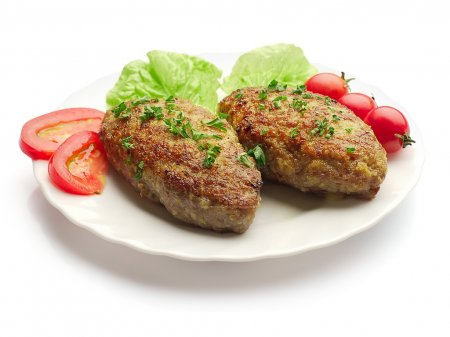 Fried meatballs decorated with salad, dill and tomatoes on the plate over white background