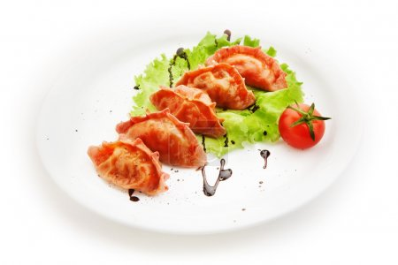 Ravioli with salad and tomato on white background