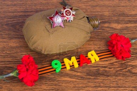 Photo pour Inscription le 9 mai dans la table, la cantine militaire, clous de girofle, médailles et ruban Grigoryevskaya - image libre de droit
