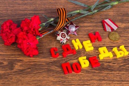 Photo pour Félicitations pour la fête de la victoire : inscription, des commandes, des médailles, des oeillets et georgievskaya ruban sur fond en bois - image libre de droit