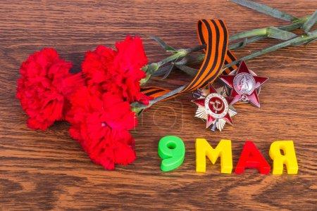 Photo pour Oeillets, médailles et l'inscription « 9 mai », ruban de St. George sur la table, nature morte à la fête de la victoire - image libre de droit
