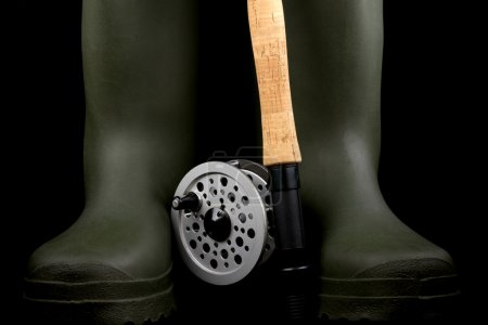 Fly Fishing Rod and Reel with Wading Boots on Black Background