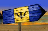 Barbados Flag on wooden table sign on beach background