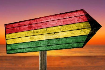 Photo pour Bolivie Drapeau sur panneau de table en bois sur la plage - image libre de droit