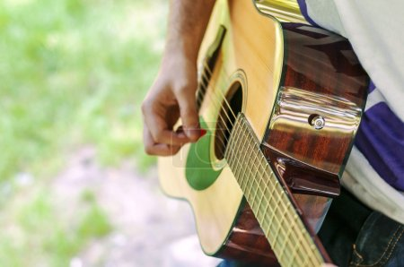 Young guitar player playing song outdoor in park