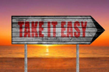 Photo pour Panneau en bois rouge Take It Easy avec sur un fond de plage - image libre de droit