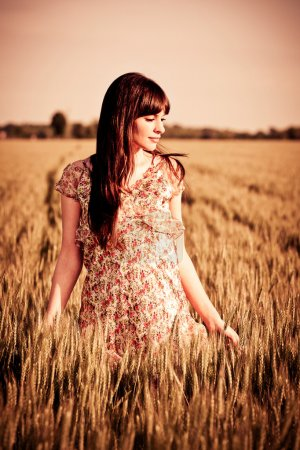 Photo pour Jeune belle femme marchant sur le terrain pendant le coucher du soleil - image libre de droit