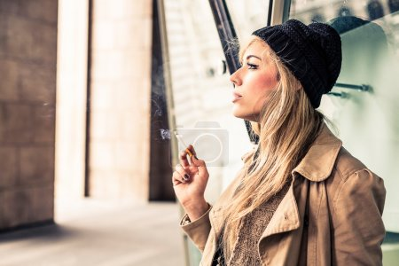 Photo for Beautiful blonde woman smoking a cigarette - Royalty Free Image