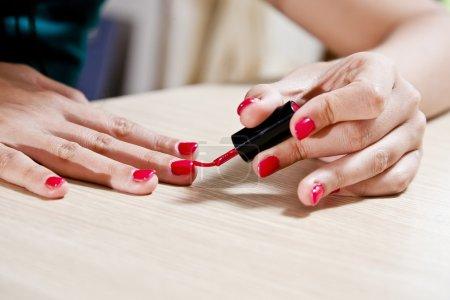 Woman painting her fingernails.