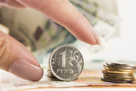 Hand takes the ruble and dollars with banks of rubles