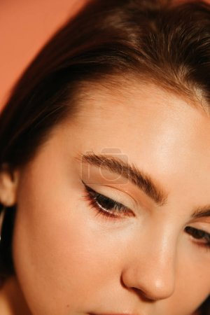 Photo for Close up of young woman cropped face with shiny summer cat eyes makeup isolated on orange - Royalty Free Image