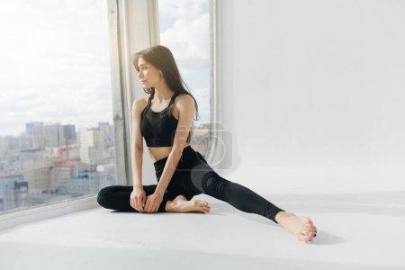 pretty armenian woman meditating in half pigeon pose while looking through window