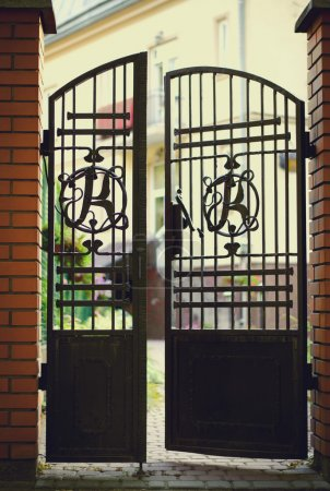 Photo for Black wrought iron and brick entrance gates with home facade in background - Royalty Free Image