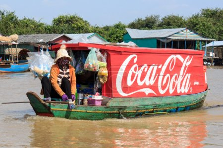 Coca Cola logo painted on wooden boat, floating village, Cambodia.