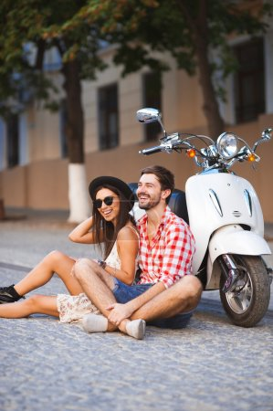 Young couple sitting near white retro scooter and smiling, happy relathionship travel concept