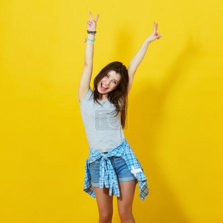 Photo pour Jeune fille écartant les mains avec joie isolé sur fond jaune vif. Adolescente insouciante posant en studio sur un mur jaune vif - image libre de droit