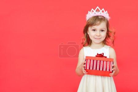 Photo pour Mignon petit préscolaire fille portrait de Noël, isolé sur rouge. enfant fille portant la couronne et robe blanche tenant une boîte-cadeau rouge, isolé sur fond rouge - image libre de droit