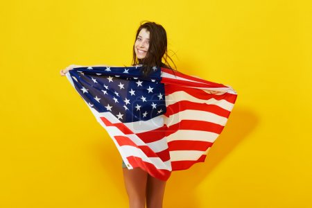 Photo for Beautiful patriotic young woman with the American flag held in her outstretched hands over bright yellow background. 4th july Independence Day concept - Royalty Free Image