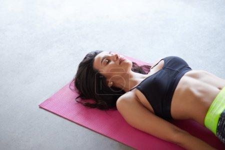 Photo pour Jeune femme pratiquant dans un studio de yoga sur tapis rose et sol en béton gris. Shavasana ou pose de corps est la fin d'une classe ou d'une pratique avec copyspace - image libre de droit