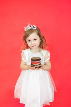 Photo for Vertical portrait of blond hair little girl holding a gift cake on red background. Cute preschoolder wearing a princess crown and white beautiful dress have a present - Royalty Free Image