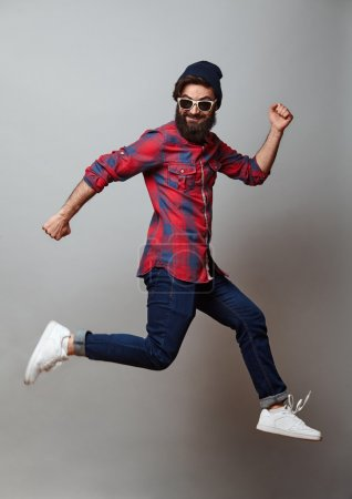 Photo for Happy excited jumping young bearded man. Funny portrait on young casual male model in humorous jump on grey background. - Royalty Free Image