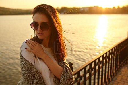 Photo pour Triste femme près d'un lac inquiet sur fond de coucher de soleil avec l'espace de copie - image libre de droit