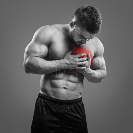 Muscular shirtless man with chest pain over gray background.