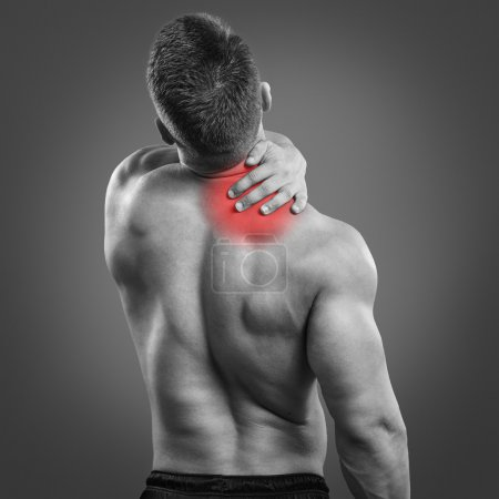 Back view portrait of a man with neck pain over gray background.