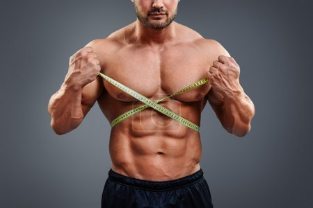 Bodybuilder measuring waist with tape measure