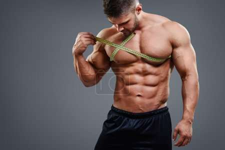 Bodybuilder measuring chest with tape measure