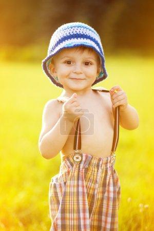Photo pour Portrait d'adorable petit garçon tenant son pantalon de bretelles - image libre de droit