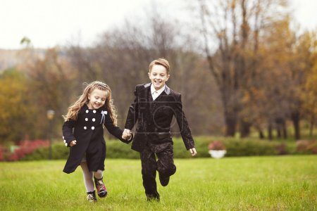 Photo for Brother and sister running in a park on autumn day. Little girl and boy holding each others hands - Royalty Free Image