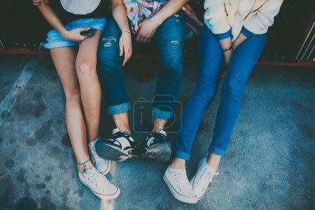 Photo pour Pieds de trois amis s'asseyant ensemble. Verticale cultivée de deux fille et un garçon détendant. Vue supérieure des chaussures des hipsters se reposant. - image libre de droit
