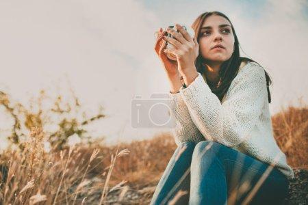 Photo pour Adolescente, assis seul sur une journée froide d'automne. Solitaire triste jeune femme portant chandail chaud. Concept de solitude et de la solitude. - image libre de droit