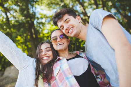 Photo for Happy teenage friends smiling outdoors on nature. Handsome young people having fun together and posing for camera. - Royalty Free Image