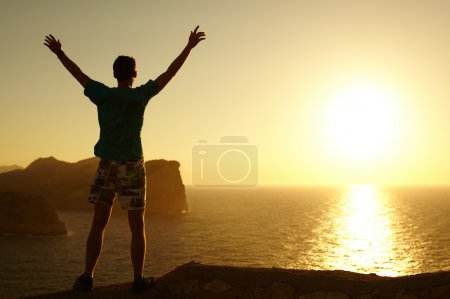 Silhouette of a man with raised arms on sunset