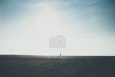 Man walking alone to horizon on black beach in Iceland leaving footprints