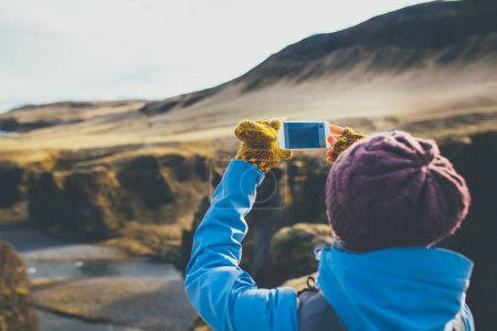 Photo for Back view of woman wearing winter clothes taking pictures of canyon in Iceland. - Royalty Free Image