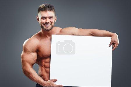 Carrossier souriant tenant une affiche blanche vierge