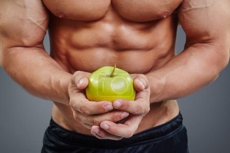 shirtless bodybuilder holding an apple