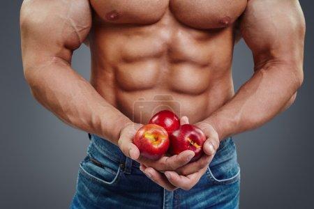 man bodybuilder hands holding a fresh peaches