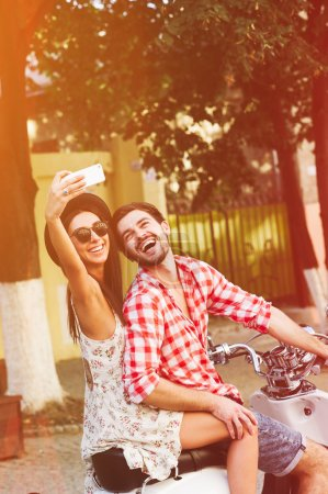 Stylish happy young couple making self picture on scooter