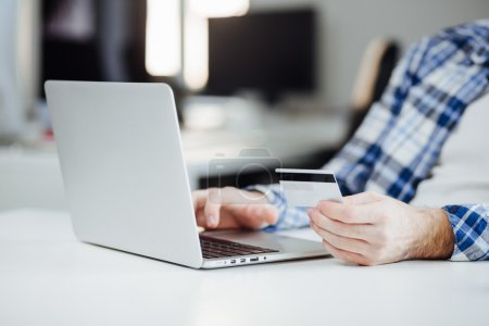 Man Shopping Online Using Laptop and Credit Card