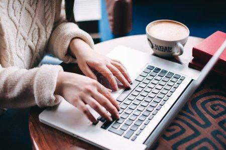 Photo pour Fermer les mains de la jeune femme tapant sur ordinateur portable tout en prenant un petit déjeuner au café avec une tasse de café - image libre de droit