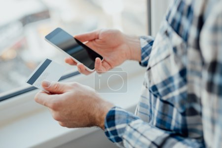 Man hands holding card and smart phone