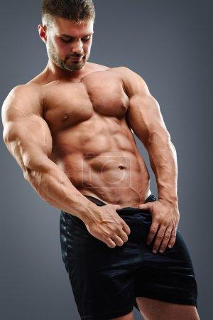 Photo pour Homme torse nu montrant ses muscles abdominaux sur fond gris - image libre de droit