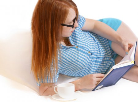 Girl reading a book on a white bed.