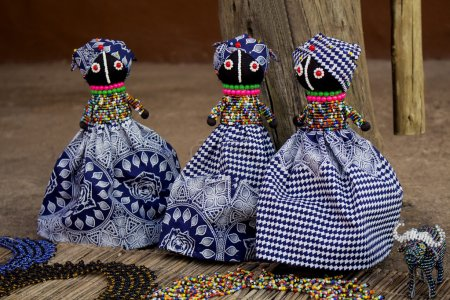 African unique rag dolls in traditional handmade colorful beads and fabrics clothes . Craftsmanship. African fashion Local craft market in South Africa.